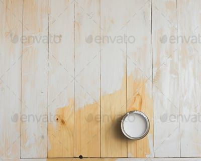 Open cans of paint on a wooden background. Partially painted with white
