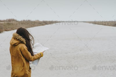 Woman reading a map next to a river, Greece.