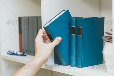 Hand taking book from the shelf
