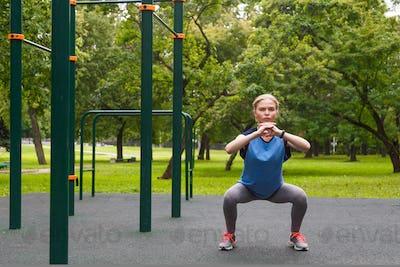 Beautiful girl doing squats outdoor sport site
