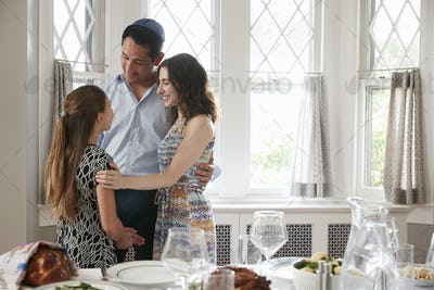 Jewish couple and daughter embracing before Shabbat meal