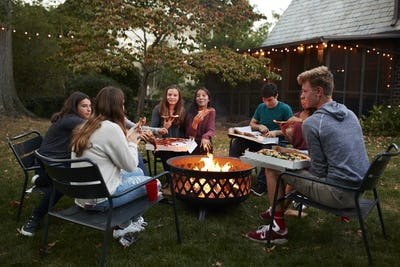 Teenage friends sit round a fire pit eating take-away pizza