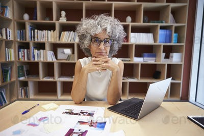 Senior businesswoman using laptop in office looks to camera