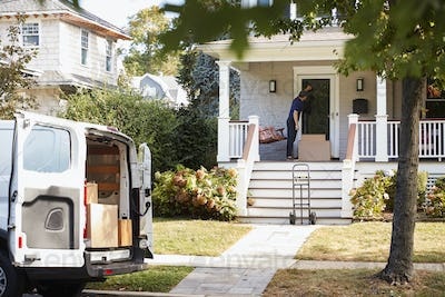 Courier Using Trolley To Deliver Package To House