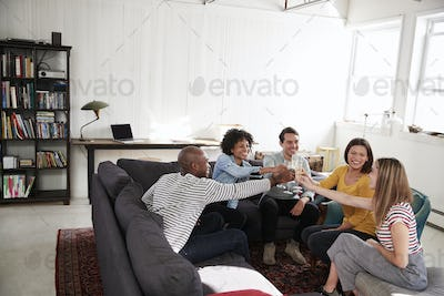 Five friends making a toast in a New York loft apartment