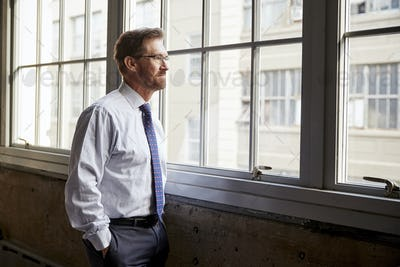 Senior businessman looking out of window, hands in pockets