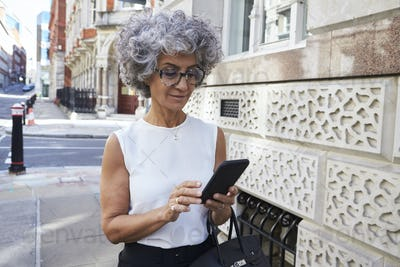 Middle aged woman using smartphone in city street