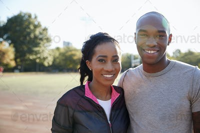 Young black couple smiling to camera in Brooklyn park