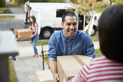 Children Helping Unload Boxes From Van On Family Moving In Day