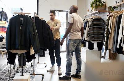 Shop assistant helping customer in a menÕs clothes shop