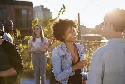 Friends talking at a rooftop party backlit by sunlight