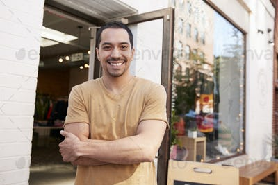 Young Hispanic shop owner smiling to camera outside his shop