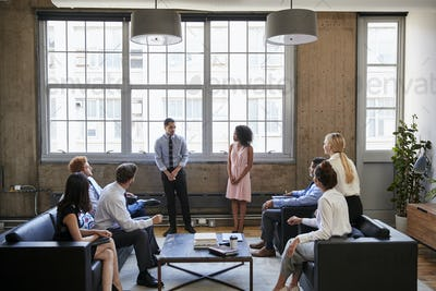Man and woman present to team at informal business meeting
