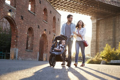 Young family with a daughter taking walk on a street