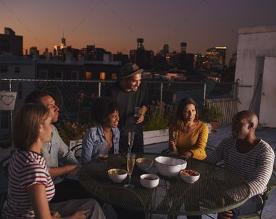 Adult friends talking at a table on a rooftop, evening