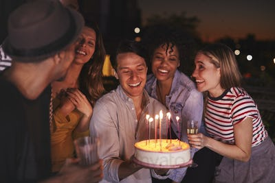 Young adults celebrating with a birthday cake on a rooftop