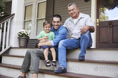Male Multi Generation Family Sitting On Steps in Front Of House