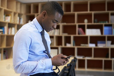 Young black man using smartphone in a boardroom, close up