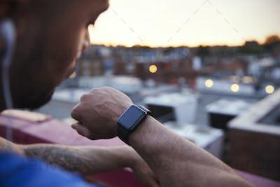 Male urban runner checks fitness app on smartwatch, close up