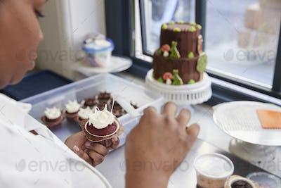 Black woman preparing food in a bakery, over shoulder view
