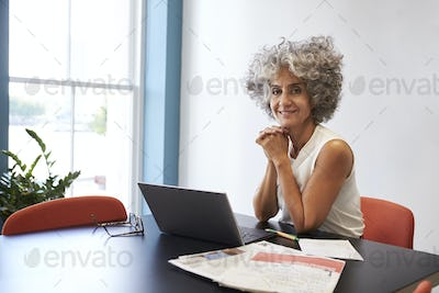 Middle aged woman working in an office smiling to camera