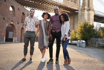 Portrait Of Friends Walking By Brooklyn Bridge In New York City