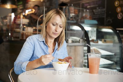 Woman In Coffee Shop Sitting At Table Eating Bowl Of Soup