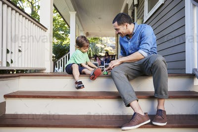 Father And Son Sit On Porch Of House Playing With Toys Together