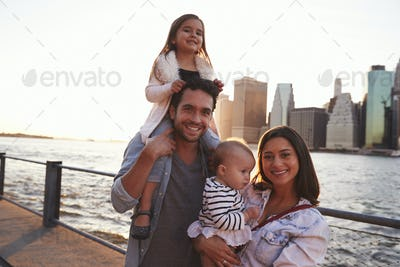 Young family with daughters standing on quayside, close up