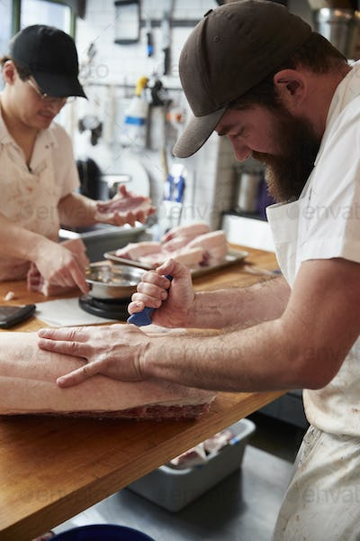 Two butchers preparing meat,cuts of meat in a butcher's shop, vertical