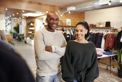 Young adult couple smiling to camera in clothes shop