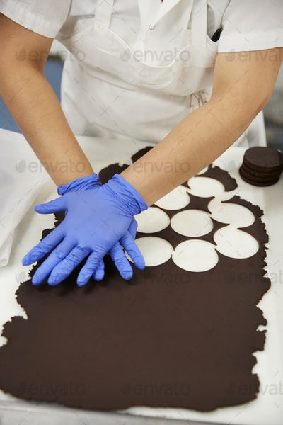 Young woman cutting out cookie dough circles at a bakery