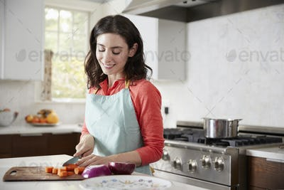 Woman chopping carrots in kitchen for Jewish passover meal