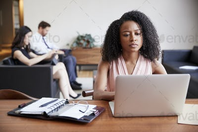 Young black businesswoman using laptop at a desk