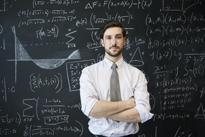 Young man looking to camera in front of a blackboard