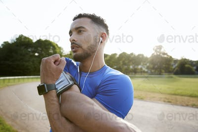 Male athlete at track stretching shoulders, close up