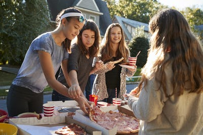 Teen girls sharing a pizza at a neighbourhood block party