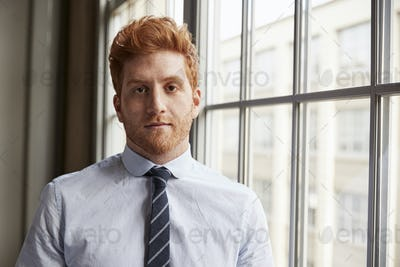 Young red haired bearded businessman looking to camera