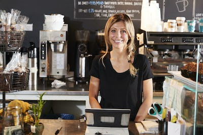 Portrait Of Female Barista Behind Counter In Coffee Shop