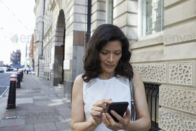 Woman in the street navigating with smartphone, waist up