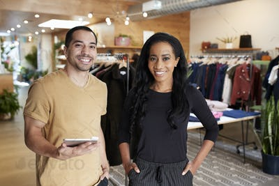 Young couple with tablet smiling to camera in a clothes shop