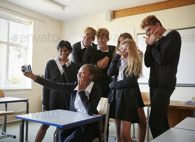 Group Of Teenage Students Posing For Selfie In Classroom