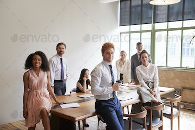 Young professionals in a meeting room looking to camera