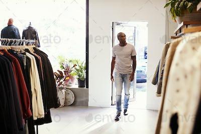 Young black man walking into a clothes shop