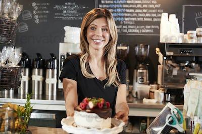 Waitress Holding Freshly Baked Cake With Buttercream Frosting