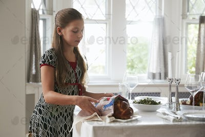 Girl covering challah bread on a table set for Shabbat meal