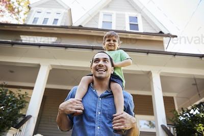 Father Giving Son Ride On Shoulders Outside House