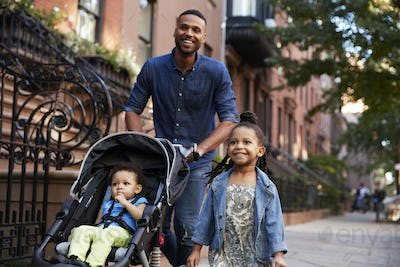 Father and two daughters taking a walk down the street, close up