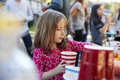Four year old girl helping herself to food at a block party