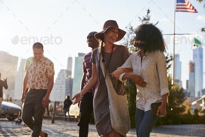 Group Of Friends Walking With Manhattan Skyline In Background